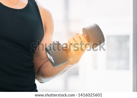 Male bodybuilder lifted the rubber dumbbell to exercise the muscles of his arms.  The device weighs 4 kilograms, helping to lift the upper arm. Sport concept.