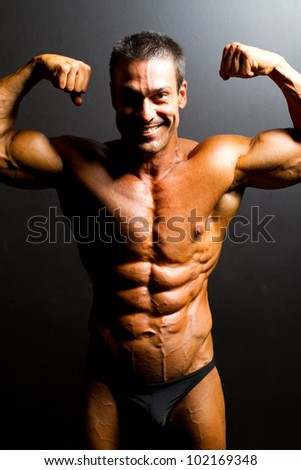 male bodybuilder posing on black background