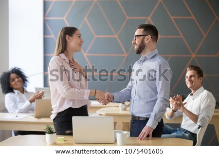 Male boss or team leader shaking hand of female successful employee congratulating with promotion or rewarding, appreciating for good work result  while business team applauding, recognition concept