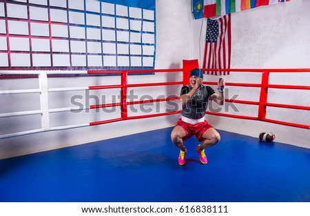 Male boxer skipping rope in a regular boxing ring surrounded by ropes in a gym #616838111