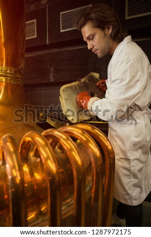 Male brewer standing near brew tank with bronzed pipes. Man holding cover of brew kettle in hands and looking down. Specialist wearing white coat and brown leather gloves.