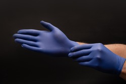 Male brown skin doctor hands put blue nitrile gloves on. Close up on a black background. CPR First AID hands in Gloves Safety Rule.