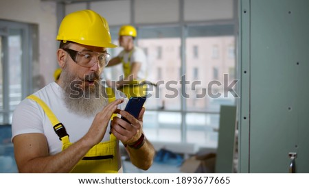 Male builder browsing mobile phone during break and doing winner gesture getting good news. Aged excited foreman in hardhat and uniform using smartphone raising fist celebrating success Photo stock ©