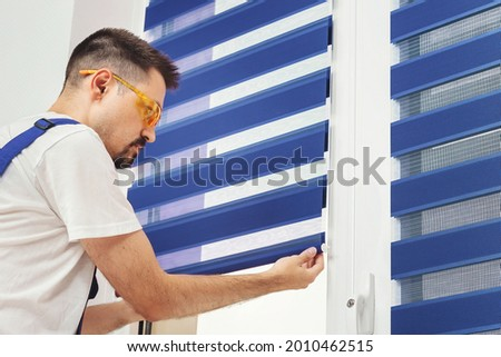 Male builder carpenter pulling down a blue jalousie on a window. Repairing and inspection fabric curtains. Duo system day and night blind. Interior decor element
