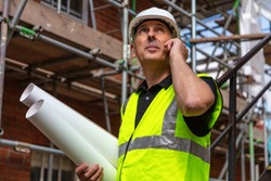 Male builder foreman, worker or architect on construction site holding building plans and talking on his cell phone