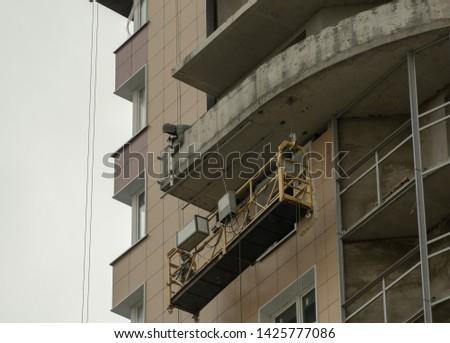 Male builder mounts a balcony fence #1425777086