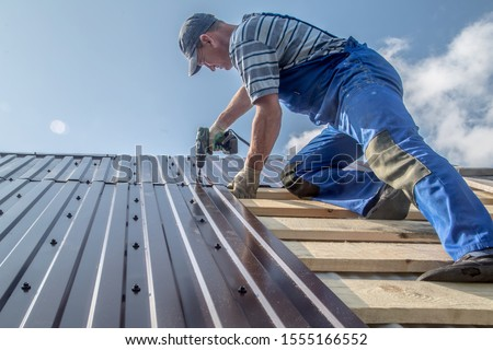 male builder performs work on the roof, fastens corrugated sheets