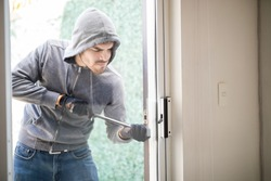 Male burglar wearing a hoodie forcing entry into a house with a plank through a back door