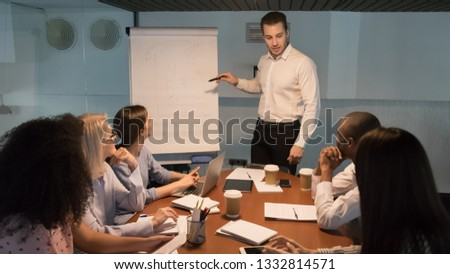 Male business manager coach speaker giving corporate presentation pointing at flip chart training employees clients, businessman mentor leader explaining financial strategy at office meeting workshop