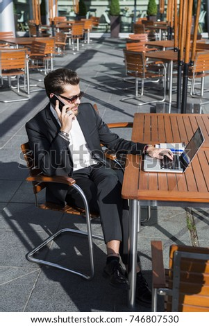 Male businessman or worker in black suit with shirt, bracelets and accessories on hands sitting outside at a wooden orange table near computer at a cafe and talking on mobile phone. #746807530