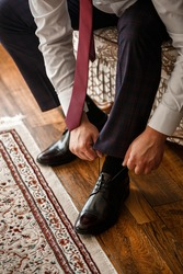 Male businessman puts on stylish shoes. Clothes for men