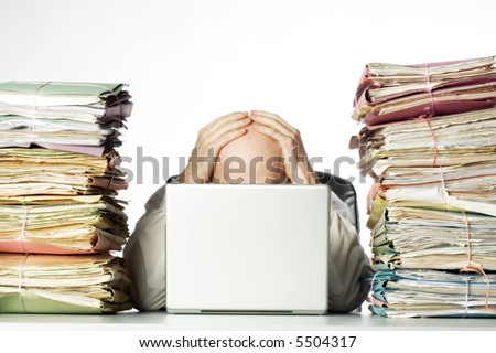 Male businessman sitting behind a laptop, his face hidden, with his hands on top of his head.  Two large piles of paperwork are piled on each side of the model, towering over his head.