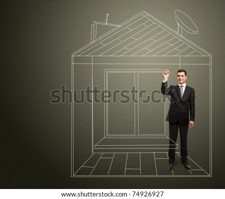male businessman with marker in fictional house writing something on glass write board