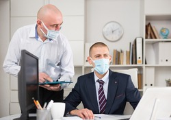 Male businessman working in an office during a pandemic makes a joint project with his business partners, discussing..the nuances