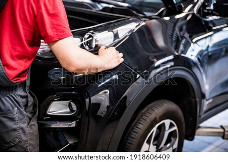 Male car mechanic at autosalon hands on black car business class at autoservice