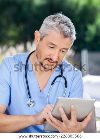 Male caretaker using tablet PC at nursing home