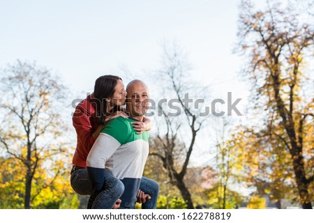 Male Carrying Smiling Female On His Back At Park