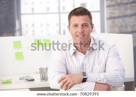 Male casual office worker smiling in office, sitting.?