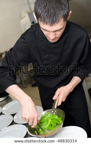 male caucasian chef in black uniform lays out green pea pods on plates