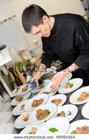 male caucasian chef in black uniform pours sauce on plates with lamb meat