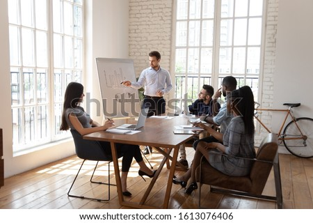 Male Caucasian coach or trainer stand making flip chart presentation to multiethnic office employees at briefing, serious businessman talk present strategy on whiteboard to diverse workers at meeting