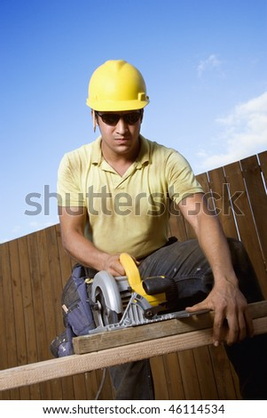 Male Caucasian construction worker in safety glasses and a hardhat cutting wood with a circular saw. Vertical shot.