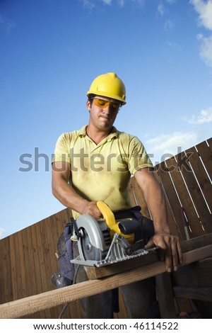 Male Caucasian construction worker in safety glasses and a hardhat. He is cutting wood with a circular saw. Vertical shot.
