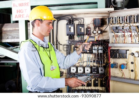 male caucasian electrician checking industrial machine control box temperature