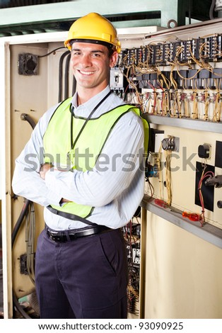 male caucasian industrial electrician portrait in front of machinery