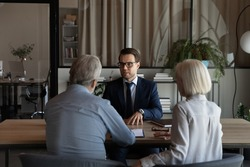 Male Caucasian specialist have meeting with mature couple clients, discuss health insurance for older people. Middle-aged spouses customers consult with relator or broker. Realty, rent concept.