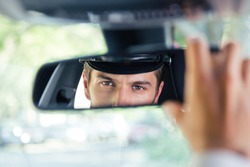 Male chauffeur sitting in a car and looking at his reflection in a mirror