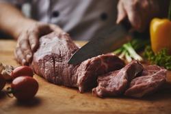 Male chef cutting big piece of beef on wooden board in restaurant kitchen. Man cook preparing steak and vegetable garnish.