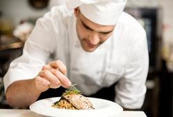 Male chef garnishing his dish, ready to serve