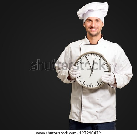 Male Chef Holding Wall Clock Isolated On Black Background