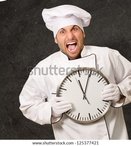 Male Chef Holding Wall Clock On Wall - stock photo