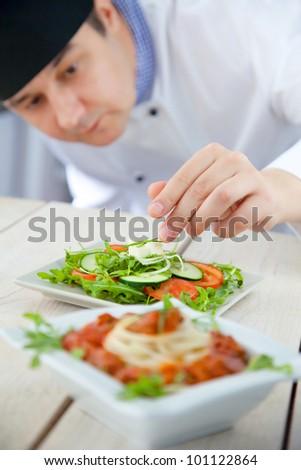 Male chef in restaurant kitchen is garnishing and preparing pasta dish