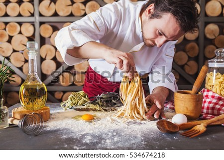 Shutterstock Male chef making homemade pasta with flour and eggs over old wooden table