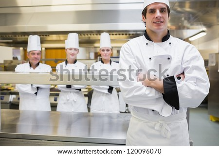 Male chef standing in kitchen with team behind him