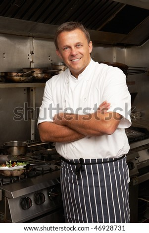 Male Chef Standing Next To Cooker In Restaurant Kitchen
