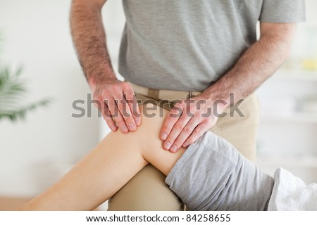 Male Chiropractor massaging a charming woman's knee in a room
