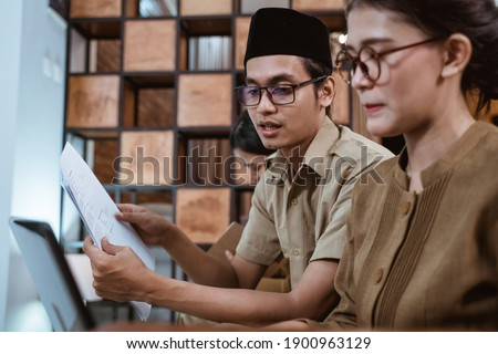 male civil servants in uniform sit holding worksheets next to female civil servants while working from home