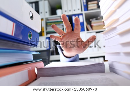 Male clerk arm trying to reach top of paper pile from below closeup. Out of time workaholic sad exhausted tired executor efficiency focus office life salvation request concept #1305868978