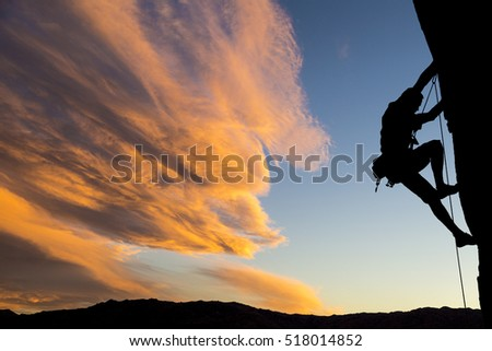 Male climber dangles from a sheer rock spire. Сток-фото ©