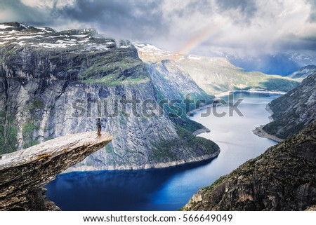 Male climber standing at the edge of cliff Trolltunga looking at rainbow against mountains, dramatic sky and amazing blue lake. Location: beautiful landscape of wild nature in Norway, Scandinavia. #566649049