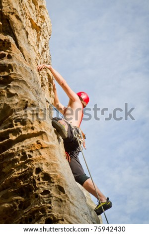 male climbing on sandstone cliff - stock photo