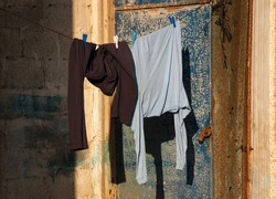 Male clothes hanging to dry outdoor of house. Rusty closed door and cement brick wall at background.