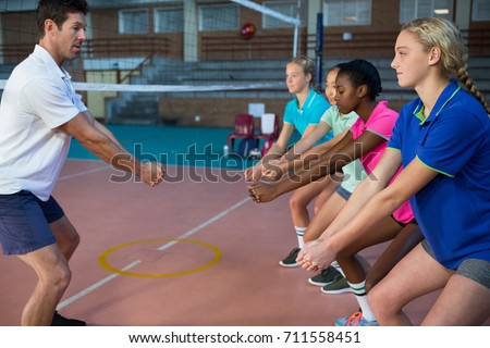 Male coach and female players performing stretching exercise in court