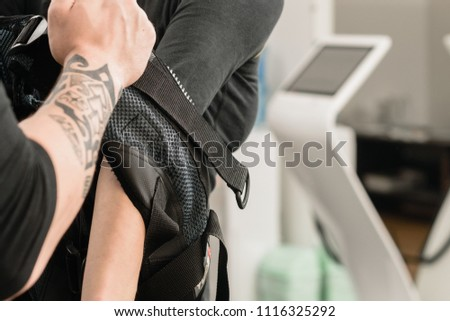 Male coach dressing woman in electro muscular stimulation vest #1116325292