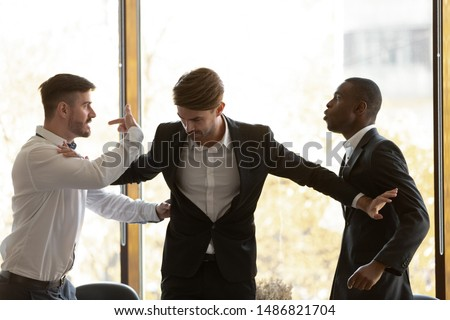 Photo of  Male colleague set apart angry diverse business men coworkers argue fighting at corporate office meeting, mad employees quarreling shouting having conflict at work, racial hatred harassment concept
