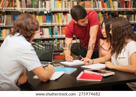 Male college student explaining some school work to his colleagues while studying in the library